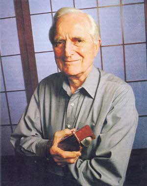 Douglas Engelbard holding early prototype of computer mouse